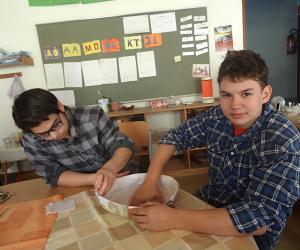 Johannes und Askin schöpfen aus Pappmaschee eine feine Paella-Pfanne