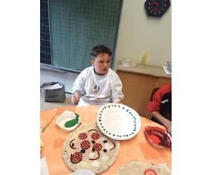 Marlon zeigt seinen fertig gemalten Teller