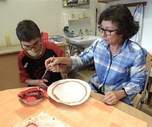 Johanna hilft Marvin dabei, den  Tellerrand schön zu dekorieren
