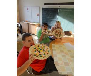 Die Pizza ist fertig: Johannes, Arcun und Gabi geniessen sie