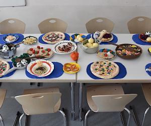 Die Nationalgerichte von Italien, Ungarn, Türkei, Belgien, Spanien, Tschechien und Dänemark nebeneinander auf dem Tisch vereint